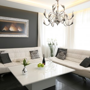 Spowity czernią salon magnetyzuje swą urodą. W tym kolorze jest zarówno tapeta na ścianie, jak i płytki na podłodze. Na ich tle  białe meble prezentują się naprawdę imponująco. Projekt: Łukasz Sałek. Fot. Bartosz Jarosz.