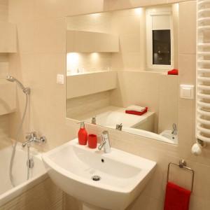 Dzięki jasnej kolorystyce oraz licznym punktom świetlnym łazienka wydaje się większa. To także zasługa podwieszanej ceramiki sanitarnej. Przestrzeń powiększa także lustro nad umywalką. Projekt: Iza Szewc. Fot. Bartosz Jarosz.