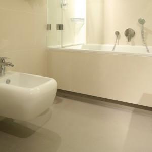 Aby łazienka, w której dominuje beżowy kolor okładzin nie wydawała się monotonna, na podłodze zastosowano nieco ciemniejszy odcień beżowego gresu. Projekt: Małgorzata Borzyszkowska. Fot. Bartosz Jarosz.