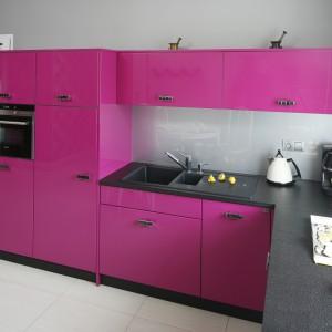 Zabudowę kuchenną wykończono w kolorze intensywnej fuksji. Żywe barwy tonują różne odcieni szarości - na blacie kuchennym i ścianach. Fot. Bartosz Jarosz.