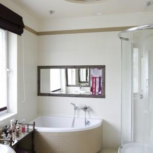 W łazience dominują obłe, zaokrąglone kształty. Takie są wanna, umywalka i kabina prysznicowa. Korespondują one ze sklepieniem na suficie. Całość wykończono w lekkim stylu glamour, z ozdobnym oświetleniem. Fot. Bartosz Jarosz.