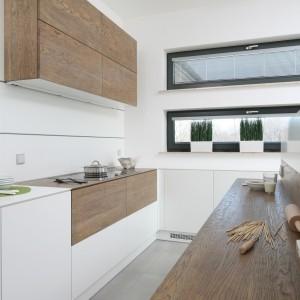 Kuchnia w bieli, ocieplonej drewnem. Tutaj powierzchnia nad blatem kuchennym została wykończona tym samym MDF-em co zabudowa kuchenna. Projekt: Konrad Grodziński. Fot. Bartosz Jarosz.