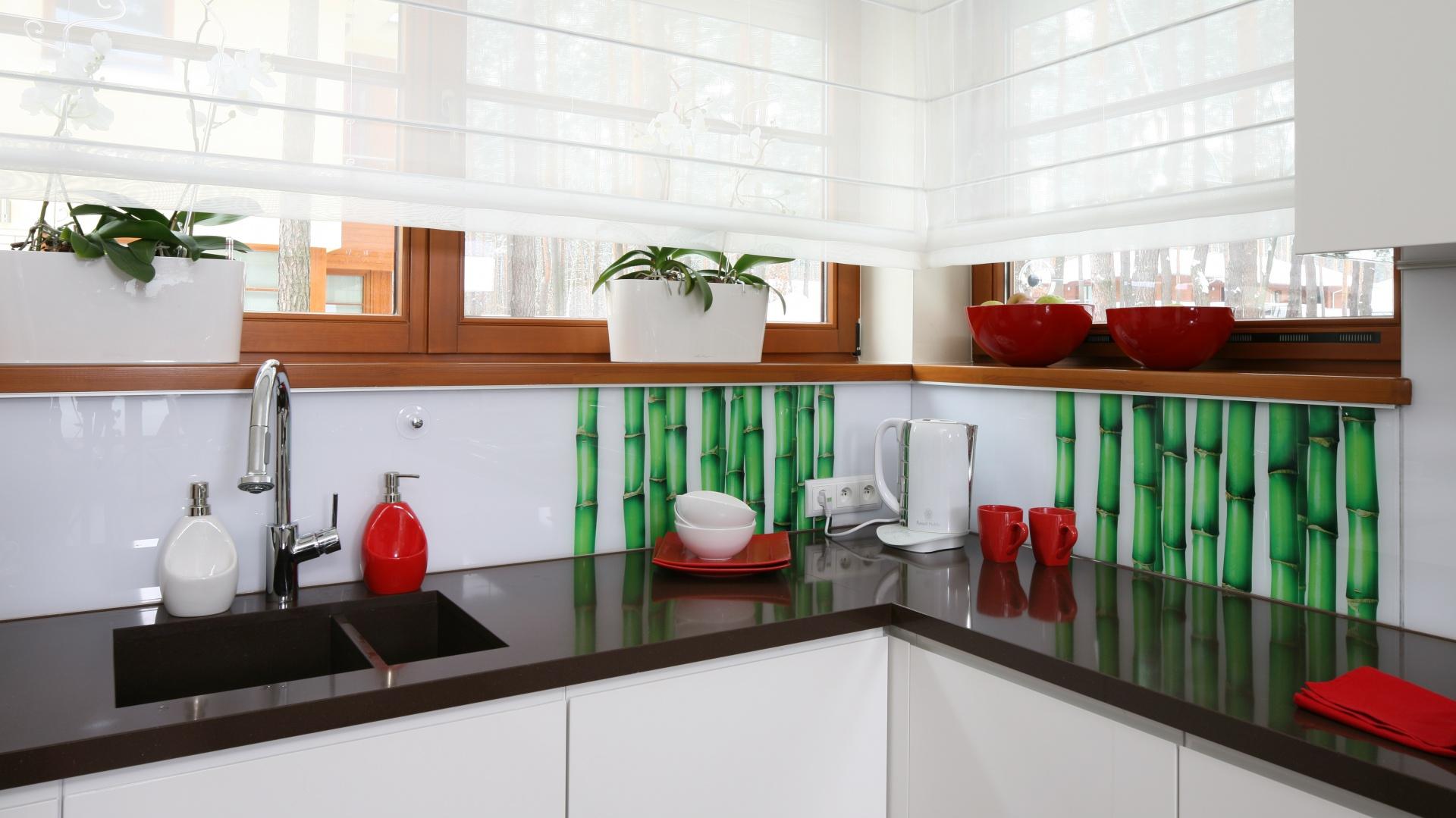 Ciemny blat i białe fronty szafek ożywiono kolorowymi dodatkami oraz przyciągającym wzrok akcentem dekoracyjnym w postaci fototapety z grafiką soczystego zielonego bambusa. Projekt: Katarzyna Mikulska-Sękalska. Fot. Bartosz Jarosz.