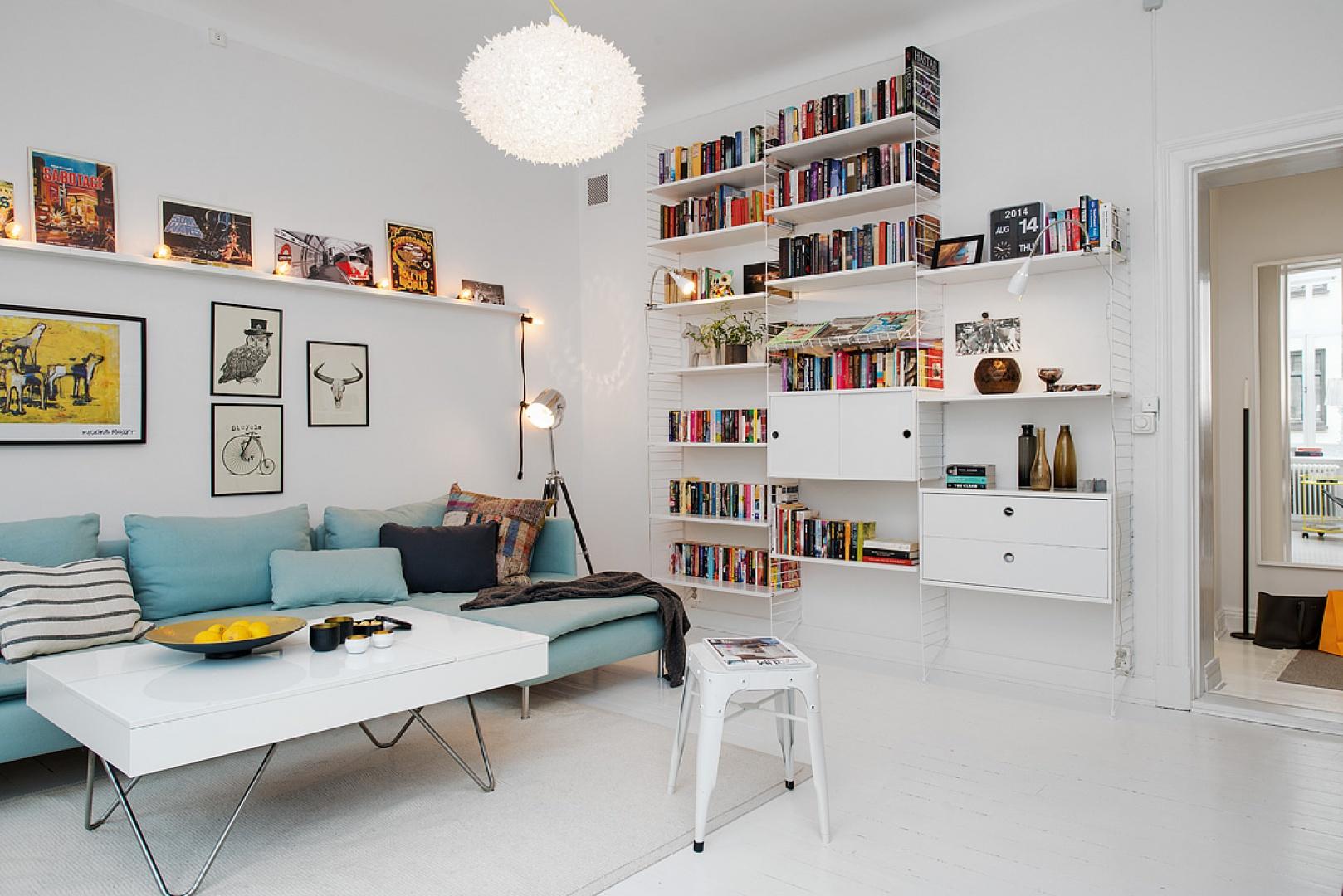Błękitna sofa w połączeniu z jasnymi meblami i kolorami ścian tworzy typowo skandynawskie wnętrze. Fot. Alvhem Mäkleri.