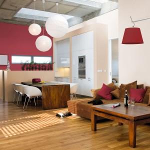 Ciepłe stonowane odcienie czerwieni w połączeniu z naturalnym drewnem strworzą przytulną, jesienną aurę w salonie. Fot. Tikkurila.