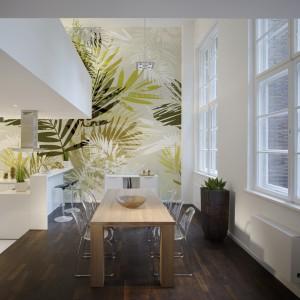 Wspólną ścianę kuchni i jadalni pokryto fototapetą z roślinnym wzorem. Spaja ona wizualnie otwartą przestrzeń jadalni i kuchni, stanowiąc główny efekt dekoracyjny. Fot. JVD.