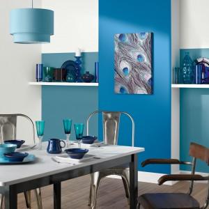 Ścianę w jadalni pomalowano dwoma różnymi odcieniami błękitu. Ciemniejszą barwą wykończono wyeksponowaną, lekko wysuniętą do przodu część ściany, a po jej obu stronach zastosowano jaśniejszy, lekko przydymiony odcień niebieskiego. Całość komponuje się z dekoracjami i lampą nad stołem jadalnianym, tworząc barwną, estetyczną kompozycję. Fot. Crown Paints.