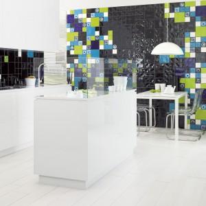 Jadalnia i kuchnia stanowią wspólną otwartą przestrzeń. Stół jadalniany koresponduje kolorystyką i stylem z nowoczesnymi meblami kuchennymi, a ściana w jadalni została wyłożona tym samym materiałem co powierzchnia nad blatem kuchennym. Intensywne, soczyste kolory ożywiają białe wnętrze. Fot. Ceramika Paradyż.