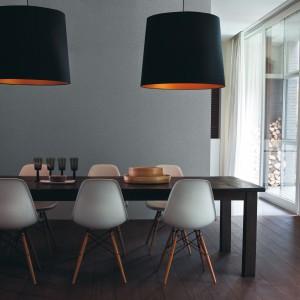 Stonowane szarości na ścianie tej jadalni pasują kolorystycznie do krzeseł przy stole. Nowoczesna, chłodna estetyka przełamana została pomarańczowymi wnękami abażurów. Fot. Para Paints.