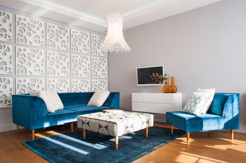 Pokój dzienny skomponowano z bieli i różnych odcieni niebieskiego. Turkusowe meble wypoczynkowe pięknie kontrastują z oryginalnymi, ażurowymi panelami na ścianie. Projekt: Arkadiusz Grzędzicki. Fot. Adam Ościłowski, panadam.pl.