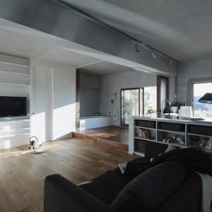 Wokół strefy z telewizorem zlokalizowano schowek oraz drzwi do toalety. Na i pod sprzętem TV zlokalizowano niewielkie półki. Biały kolor zabudowy optycznie powiększa wnętrze. Po zewnętrznej stronie półwyspu kuchennego zaplanowano praktyczne, pojemne półki. Fot. Koichi Torimura.