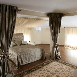 Klasycznie upięte zasłony efektownie wydzielają przestrzeń do spania. Nad łóżkiem znajduje się lekka tkanina pełniąca rolę baldachimu. Takie rozwiązanie dodaje wnętrzu przytulności. Projekt: Małgorzata Goś. Fot. Bartosz Jarosz.