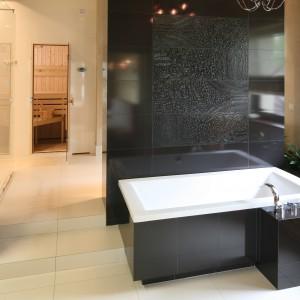 Ta imponująca metrażem łazienka dla dwojga  została nawet podzielona na dwie części. W pierwszej, z której częściej korzysta pani domu znalazła się wanna i umywalka. Projekt: Dominik Respondek. Fot. Bartosz Jarosz.