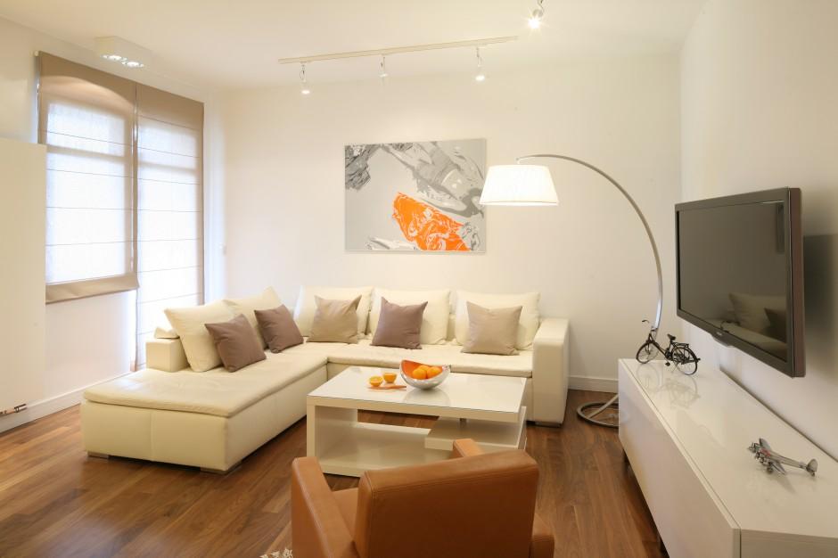 Dominujący w mieszkaniu jasny kolor ciekawie przełamują elementy w różnych odcieniach brązu oraz pomarańczowe dekoracje. Fot. Bartosz Jarosz.
