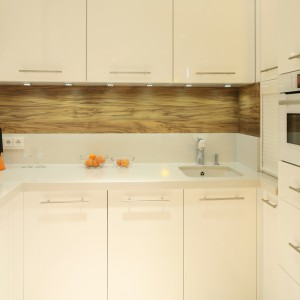 Chłodny wystrój kuchni ociepla ściana nad blatem wykończona płytą laminowaną w kolorze orzecha włoskiego. Fot. Bartosz Jarosz.