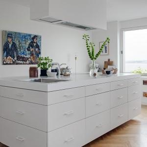 Do bieli i formy wyspy dopasowano kształt i kolor okapu kuchennego. Biała jest także bateria zlewozmywakowa. Ostre krawędzie, geometryczne kształty i gładki blat nadają pomieszczeniu nowoczesnego charakteru.  Fot. Alvhem Makleri.