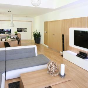 Otulone drewnem wnętrze przełamano białymi akcentami. Biała obudowa pokrywa całą ścianę kuchenną, która zamyka długą, łączoną przestrzeń salonu, jadalni i kuchni. Projekt: Małgorzata Błaszczak. Fot. Bartosz Jarosz.