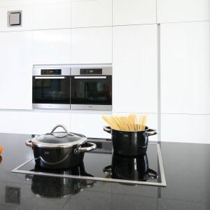 Biała zabudowa estetycznie kontrastuje z ciemnym blatem kuchennym. Tworzy jedną powierzchnię z obudowanym sprzętem AGD, który zlokalizowano na wygodnej dla domowników wysokości. Projekt: Izabella Korol. Fot. Bartosz Jarosz.