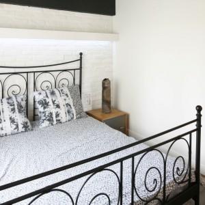 Jasne ściany kontrastują z dekoracyjną formą kutego łóżka. Projekt: Dominik Respondek. Fot. Bartosz Jarosz.
