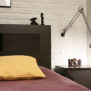 Ciemne łóżko oraz stolik nocny kontrastuje z jasną, ceglaną ścianą. Projekt: Iza Szewc. Fot. Bartosz Jarosz.