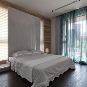Elementem przyciągającym wzrok w sypialni jest duży tekstylny zagłówek za łóżkiem, rozciągający się niemal pod sam sufit. Fot. Kyle You.