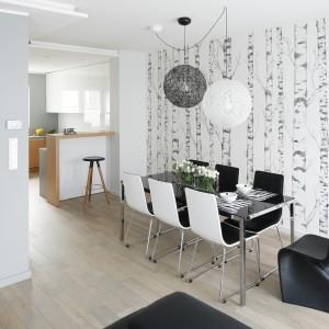 Prosta forma stołu jadalnianego równoważy odważny projekt jednego z krzeseł. Czarny połyskujący blat pięknie komponuje się z czarno-białymi krzesłami. Projekt: Beata Kruszyńska. Fot. Bartosz Jarosz.