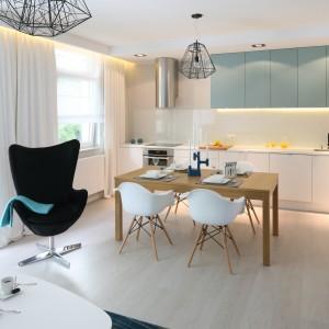 W jasnej, świeżej aranżacji otwartej przestrzeni stół jadalniany pełni funkcję elementu delikatnie oddzielającego kuchnię od salonu. Projekt: Anna Maria Sokołowska. Fot. Bartosz Jarosz.