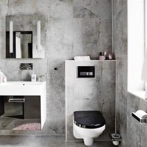 Delikatne akcenty w kolorze pastelowego różku bardzo subtelnie ożywiają szarą łazienkę. Fot. Vastanhem.