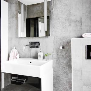 Szare płytki w łazience, ostre kubistyczne formy, oszczędne dekoracje i lustro pozbawione ram wprowadzają surowy klimat do pomieszczenia. Fot. Vastanhem.