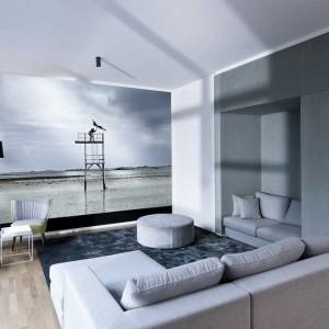 W salonie królują stonowane odcienie szarości. Głównym punktem aranżacji jest piękna fototapeta na ścianie z widokiem na jezioro, utrzymana w kolorystyce wnętrza. Fot. www.suite030.com.