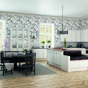 Piękna monochromatyczna kuchnia, w której kompozycję czerni i bieli przełamano ciepłym, drewnianym parkietem. W aranżację idealnie wpisują się klasyczne białe meble z drewnianym blatem na wyspie oraz czarnym odpowiednikiem pod ścianą. Fot. HTH, model Scandinavian Classic.