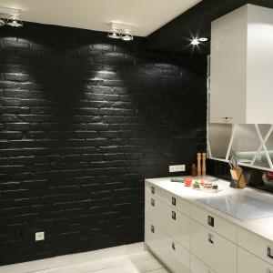 Na ścianie w kuchni jest cegła, którą pomalowano całkowicie na czarno. Faktura cegły i czarny kolor wprowadzają surowy klimat do wnętrza i kontrastują z gładkimi, białymi meblami kuchennymi. Projekt: Dominik Respondek. Fot. Bartosz Jarosz.