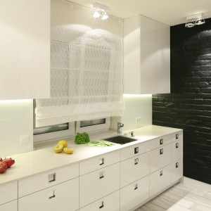 Nowoczesna biała kuchnia zyskuje charakter w połączeniu z czarną ścianą z cegły. Monochromatyczne sterylne wnętrze ocieplono podłogą z desek imitujących drewno. Projekt: Dominik Respondek. Fot. Bartosz Jarosz.