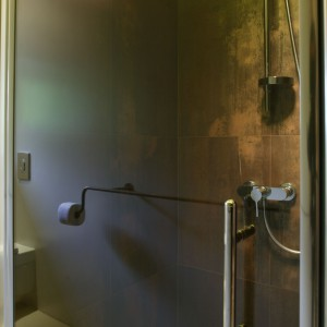 Podział łazienki na strefy za pomocą ścianek działowych wyznaczył także miejsce na prysznic. Zamiast tradycyjnej kabiny wystarczyło zamknąć wnękę drzwiami prysznicowymi. Fot. Bartosz Jarosz.