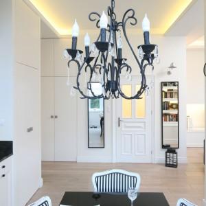 """W urządzonym z klasyczną manierą wnętrzu strefa wejścia jest niezwykle elegancką. Zdobią ją dwa wąskie lustra, w których """"przeglądają"""" się kuchnia i salon. Projekt: Małgorzata Galewska. Fot. Bartosz Jarosz."""