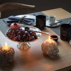 Elegancka zastawa stołowa nabiera grozy dzięki zastosowaniu kilku detali. Czarne kubki z nadrukiem czaszki i ozdobne świeczniki w jej kształcie nadają całej aranżacji grozy... Fot. Zara Home.