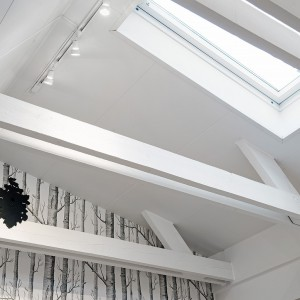 Pod sufitem pozostawiono odsłonięte belki stropowe. Zyskano dzięki temu więcej przestrzeni, zainstalowano okno dachowe, doświetlające wnętrze, a przede wszystkim białe belki stanowią element dekoracji wnętrza. Fot. Alvhem Makleri.