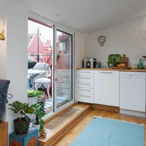 Szklane drzwi prowadzące na balkon rozcierają granicę pomiędzy wnętrzem mieszkania, a jego otoczeniem. Dzięki temu przestrzeń wydaje się większa. Fot. Alvhem Makleri.