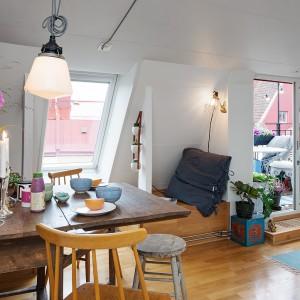 Kuchnia i jadalnia tworzą wspólną przestrzeń. Miejsce jadalni wyznacza rozkładany drewniany stół i farba tablicowa na ścianie. Fot. Alvhem Makleri.
