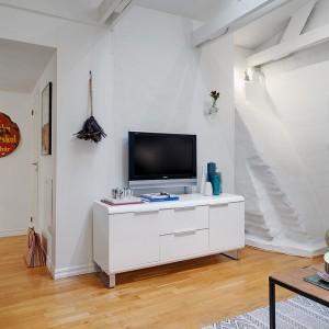 Na pionowej ścianie w salonie zlokalizowano telewizor oraz szafkę pod sprzęt RTV. Biały mebel wraz ze ścianą, eksponują TV. Fot. Alvhem Makleri.