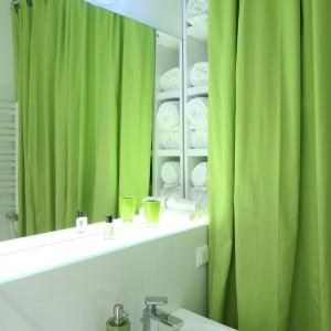 W łazience zrezygnowano z wanny, a miejsce zostało wykorzystane do urządzenie wygodnej strefy przechowywania. Regał z półkami przesłania zielona kotara. Fot. Bartosz Jarosz.