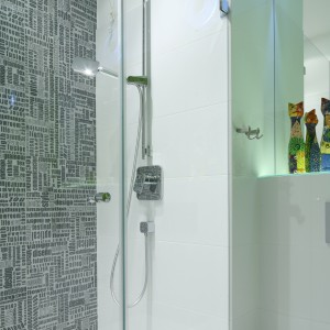 Wyposażenie wnęki prysznicowej  stanowi zestaw natryskowy z dużą słuchawką prysznicową oraz bateria podtynkowa. W posadzce zamontowano odpływ liniowy. Fot. Bartosz Jarosz.