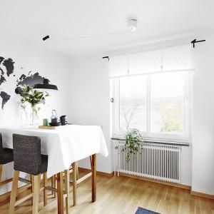 Na ścianie nad stołem kuchennym widnieje czarna naklejka z motywem kontynentów. Kolorystycznie komponuje się z ciemnymi tekstylnymi siedzeniami i oparciami krzeseł. Fot. Vastanhem.