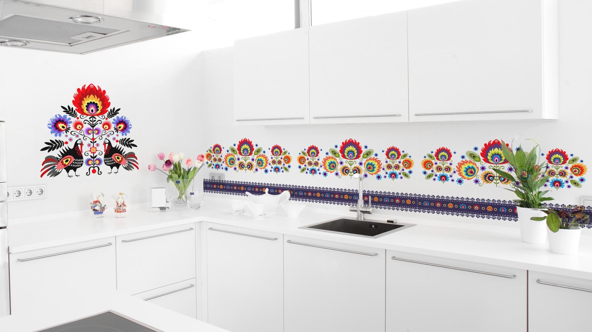 Kolejna propozycja z motywem ludowym. Białą nowoczesną kuchnię z gładkimi frontami i minimalistycznymi formami urozmaica kolorowy wzór ludowy - w większej i mniejszej wersji. Fot. Livingstyle.pl