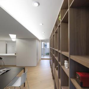 Kuchnię zlokalizowano w kubiku sąsiadującym z salonem, jadalnią i przejściem na balkon. Po zewnętrznej stronie zlokalizowano domowy bar. Fot. KC Design Studio.