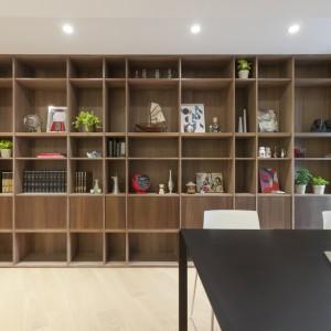 Właściciele domu dużo podróżują i przywożą ze swoich eskapad masę pamiątek. Ważnym punktem projektu było zatem wygospodarowanie miejsca, eksponującego kolekcję zebranych przedmiotów. Pokrywające cała ścianę drewniane półki o zróżnicowanej szerokości okazały się być idealnym rozwiązaniem. Fot. KC Design Studio.