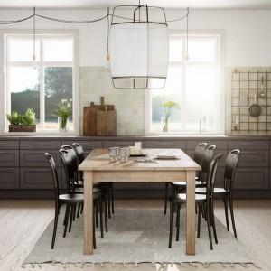 W przestronnej klasycznej kuchni stół jadalniany stanowi centrum pomieszczenia. Wykonany z jasnego drewna koresponduje kolorystycznie z płytkami na ścianie, podczas gdy krzesła wykonano w kolorze mebli kuchennych. Fot. Ballingslov, linia Grand.