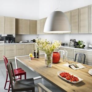 Klasyczne drewno przyjęło formę lekko zdobionych, nowoczesnych frontów bez uchwytów. Stół utrzymano w prostej stylistyce i tym samym kolorze co szafki kuchenne. Życia aranżacji dodają kolorowe krzesła. Fot. ZAJC kuchnie, Kuchnia Z6/003.