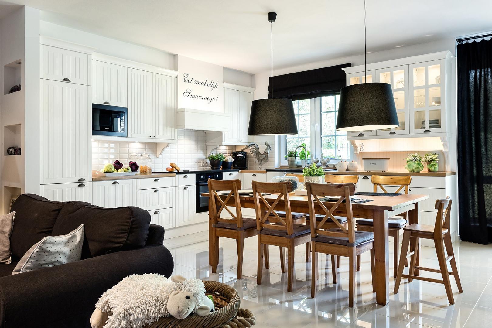 Projekt kuchni z jadalnią, nawiązujący do skandynawskiej stylistyki. Klasyczny drewniany stół i białe matowe meble z pionowym frezowaniem tworzą urokliwy zestaw. Fot. Pracownia Mebli Vigo, Max Kuchnie, Artur Krupa.