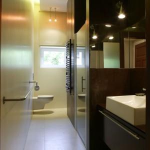 To bardzo wąskie i długie wnętrze zostało podzielone na strefy za pomocą ścianek działowych. Jedna z nich mieści umywalkę, druga prysznic, a za nim znajduje się zabudowa z pralką. Projekt: Ola Wołczyk. Fot. Bartosz Jarosz.